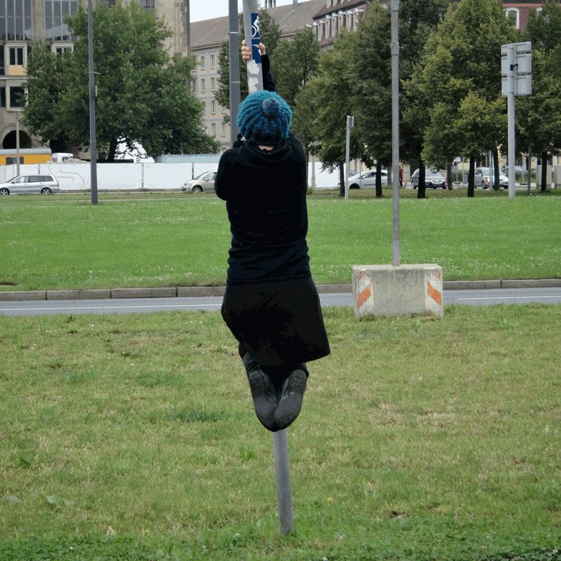 """Rückenansicht der One Minute Sculpture """"Beschilderung"""" von Eva Olivin: Die Künstlerin klammert an einer Straßenschild-Stange, mit angezogenen Beinen verharrt sie so einen halben Meter über dem Grünstreifen einer Straße."""