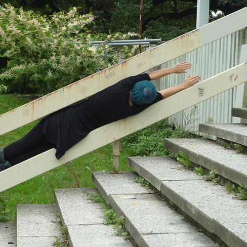 """Rückenansicht der One Minute Sculpture """"Halbe Treppe"""" von Eva Olivin: Die Künstlerin klemmt in ausgestreckter Haltung passgenau in der Lücke zwischen den beiden Metall-Streben eines Treppengeländers."""