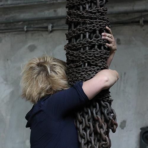 "Rückenansicht der One Minute Sculpture ""Rettungskette"": Eva Olivin klammert sich an einen Strang öliger Industrieketten."