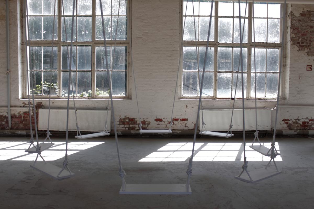 In einer stark verwitterten Industriehalle hängen 8 strahlend weiße, im Oktagon angeordnete Schaukeln.