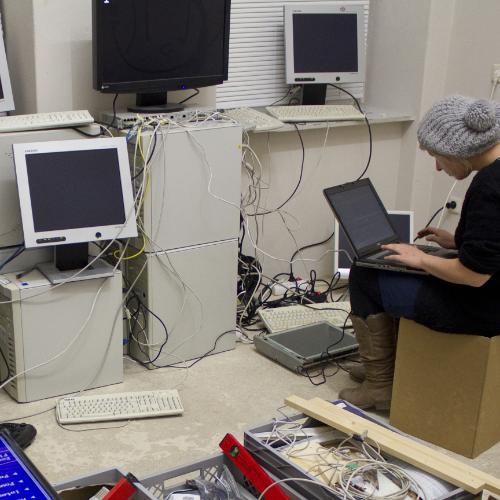 In einem chaotischen Raum mit Werkzeugen und vielen Computern arbeitet eine junge Frau an Quellcode.