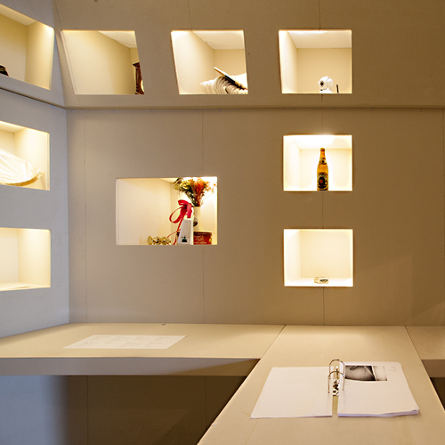 In einer Einbauwand mit 9 beleuchteten Schaukästen sind Alltagsobjekte präsentiert.