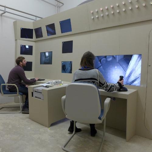 2 junge Menschen arbeiten in einem Kontrollraum mit 9 Monitoren.