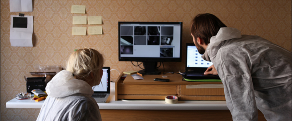 2 Leute in weißen Schutzanzügen blicken auf Notebooks und einen externen Monitor, der 10 Kamera-Bilder gleichzeitig anzeigt.