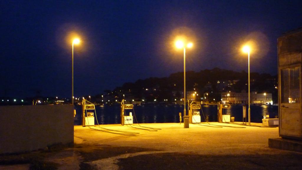 Tankstelle bei Nacht: 4 Zapfsäulen stehen direkt am Wasser.
