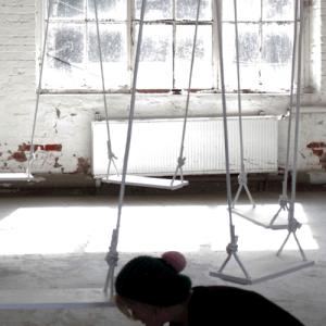 Eva Olivin arbeitet gebückt an der Installation, 5 von 8 Schaukeln hängen schon.