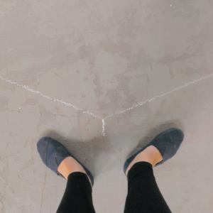 Mit Kreide ist ein stumpfer Winkel auf dem Steinboden angezeichnet. Ein Fußpaar ist im gleichen Winkel ausgerichtet.