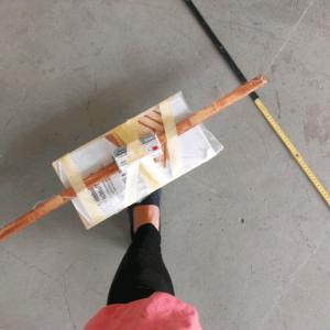 Ein Zollstock liegt auf dem Steinboden. Darüber hängt eine improvisierte Schaukel an dünnen Fäden.