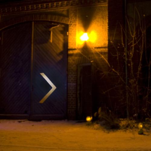 An einer Gebäudefassade weisen ein reflektierender Pfeil und Positionsleuchten den Weg zu einer schmalen geöffneten Tür.
