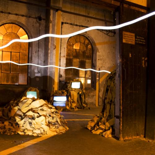 Eine schwebende Lichtspur, die in knapp 2 Meter Höhe verläuft, führt in einen großen düsteren Raum mit gelb reflektierenden Streifen. Einige verlaufen als saubere Linien, andere sind zu Bergen aufgetürmt, aus denen Monitore leuchten.
