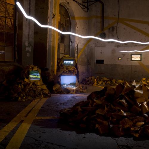 In einer dunklen Halle liegen bergeweise gelbe Straßenmarkierungsstreifen, aus einigen leuchten Videos hervor. Eine weiße Lichtspur schwebt quer durch den Raum.