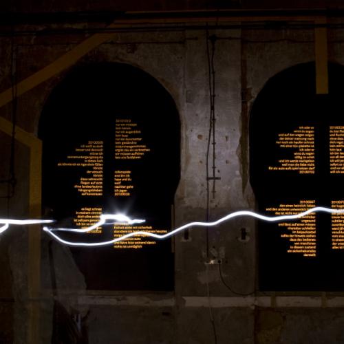 Auf einer dunklen Hallenwand verlaufen gelbe Straßenmarkierungsstreifen. Sie gehen in goldgelb reflektierende Blöcke aus rechts- und linksbündig gesetzten Texten über. Eine weiße Lichtspur schwebt im Vordergrund durch den Raum.