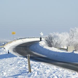 Eine kurvige Brücken-Auffahrt ist frisch vom Schnee beräumt, der sich hoch an den Rändern türmt. Ein Mensch mit einem Strauß weißer Ballons kommt von der Brücke herunter.