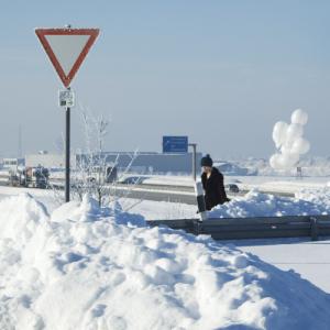 Eine junge Frau mit einem Dutzend weißer Ballons läuft von einer Autobahn auf eine Kreuzung zu. Das Vorfahrt-gewähren-Schild ragt aus einer Schneewehe.