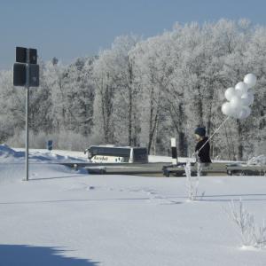 Neben einer Autobahn ragt die Leitplanke einer Seitenstraße aus dem Schnee hervor. Auf der Fahrbahn läuft ein Mensch mit 9 weißen Ballons.