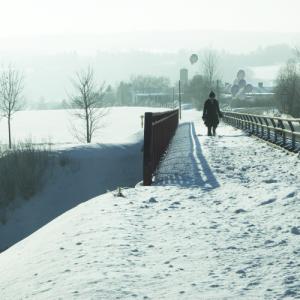 Ein weißer Ballon ist mittig an einem Brückengeländer angebunden. Eine Frau mit 7 weißen Ballons in der Hand versinkt bis zu den Knien im Schnee.