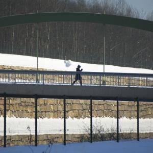 Eine Bogenbrücke führt über einen tiefen Graben. Die Silhouette einer schwarz gekleideten Person mit einigen weißen Ballons läuft mittig auf der Brücke.