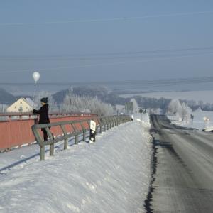 Am Straßenrand einer stark verschneiten Landschaft bindet eine Frau einen weißen Ballon an ein Brückengeländer.