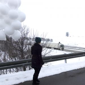 Ein Mensch mit einem Strauß weißer Ballons läuft dicht an einer Leitplanke eine verschneite Straße entlang, die über eine Autobahn führt.