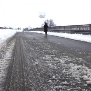 Auf einer leeren Straße liegen Eisklumpen. Im Hintergrund läuft ein Mensch mit einem Strauß weißer Ballons.