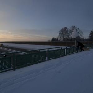 Auf der Mitte einer tief verschneiten Brücke über eine Autobahn beugt sich eine Person über das Geländer. Sie hat einen Strauß weißer Ballons in der Hand und bindet einen davon los.