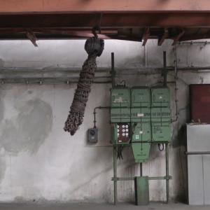 In einer Werkshalle mit alten Strom-Verteilerkästen schwingt ein riesiger Strang rostiger Ketten nach links.