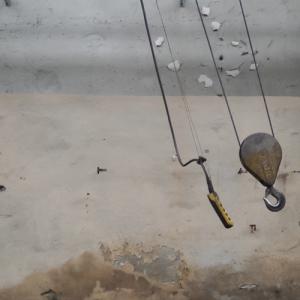 Vor einer Wand mit abblätternder Farbe schwingen ein Kranhaken und ein Steuerelement an ihren Kabeln weit nach rechts.