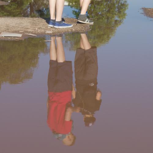 Zwei Jugendliche spiegeln sich in einer riesigen Pfütze, die ihnen den Weg versperrt.
