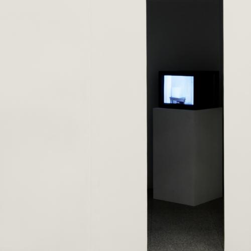 Aus einem dunklen Spalt in einer weißen Wand leuchtet ein Röhrenfernseher-Bild.