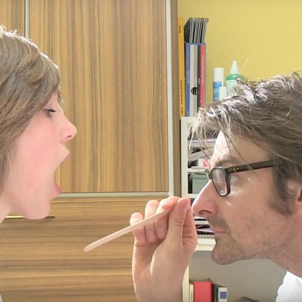 Eine Patientin öffnet den Mund weit für die ärztliche Untersuchung mit dem Holzspatel.
