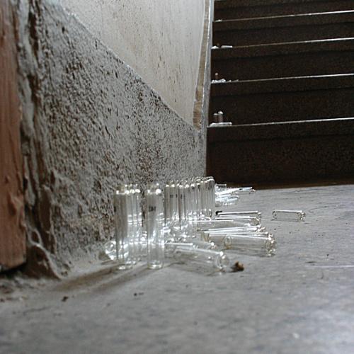 Unzählige leere Glas-Phiolen sind in einem staubigen Treppenhaus auf den Stufen und dem Etagenabsatz verteilt.