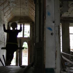 Im Treppenbereich von einem stark verfallenen Wohnhaus liegen Trümmer und Müll herum. Eine Frau, nur als schwarzer Schemen erkennbar, schaukelt mit großem Schwung durch den Raum.