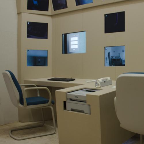 Ein Arbeitsplatz mit einer Tastatur und 9 in einer Wand eingelassenen Monitoren. In der Mittelkonsole zum benachbarten Arbeitsplatz sind Drucker und Telefon eingebaut.