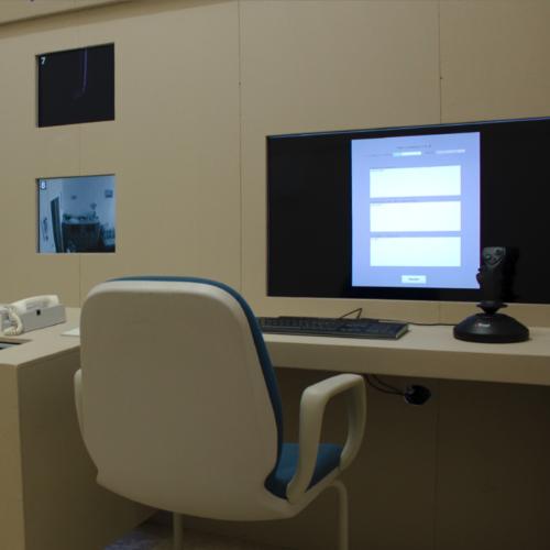 Ein Arbeitsplatz mit einer Tastatur, einem Joystick und einem fest in der Wand verbauten Monitor. Er zeigt eine Eingabemaske mit 3 Feldern.
