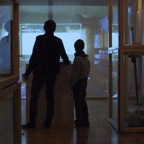 Ein Erwachsener und ein Kind stehen an einem Pult und blicken auf eine große Projektion an der Wand.