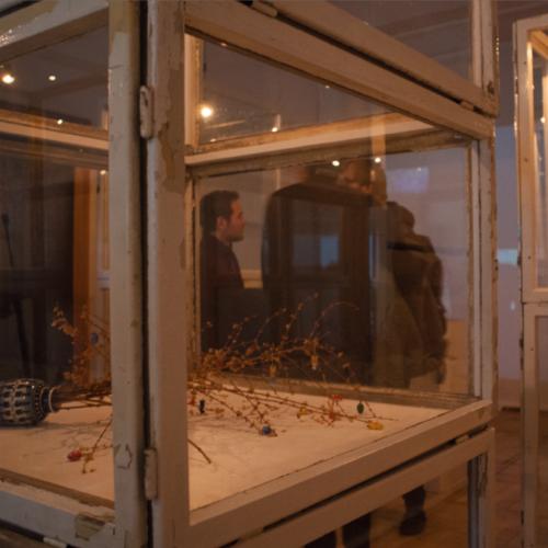 Rieisiger Schaukasten aus alten Holzfenstern, in dem ein geschmückter Osterstrauß quer liegt.