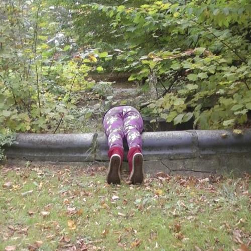 Ein Mensch steckt kopfüber in einem verwilderten Brunnen, die Beine hängen über den Rand hinaus.