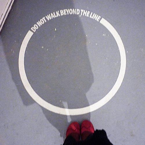 Der Schatten einer Person mit roten Schuhen fällt auf eine ringförmige Boden-Markierung mit der Inschrift: Do not walk beyond the line.